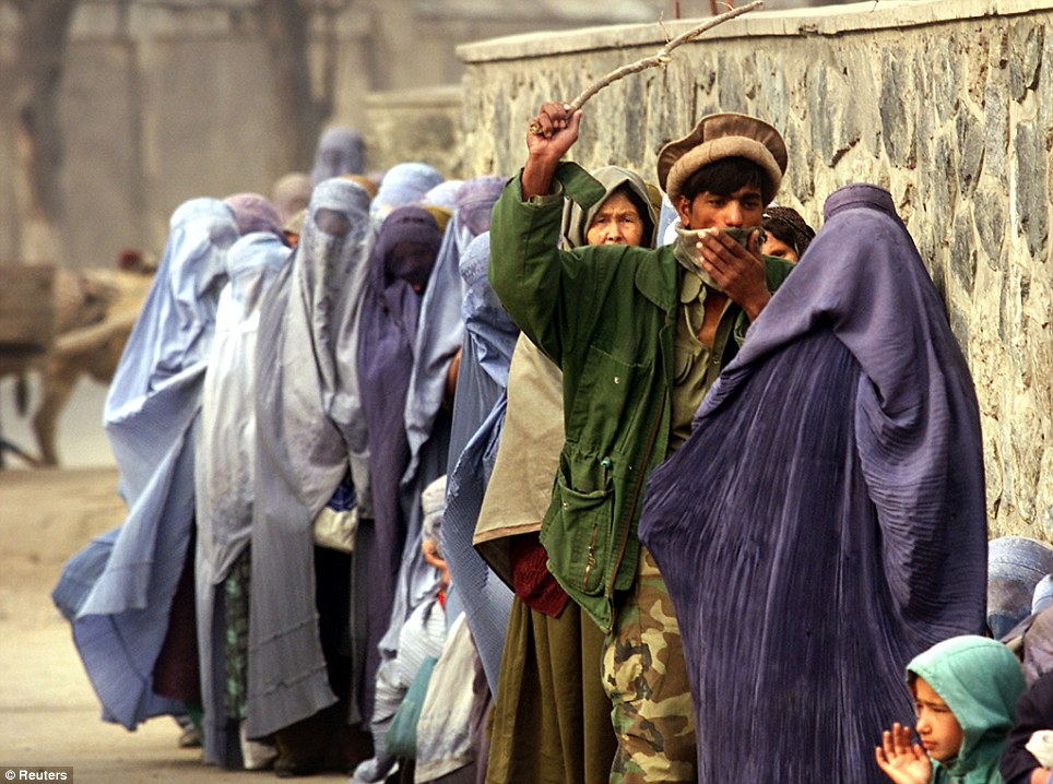 Afghan soldier uses wooden stick to maintain order at WFP distribution point in Kabul Dec 2011